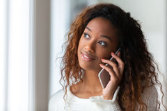 African American woman talking on a mobile phone - Black people. African American woman talking on a mobile phone  Black people Royalty Free Stock Images