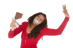 African American woman taped mouth wants chocolate Stock Image