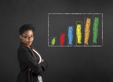 African American woman teacher or student with arms folded and chalk bar graph on black board Royalty Free Stock Image