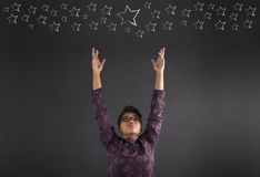 African American woman teacher or student reaching for the stars on blackboard background Royalty Free Stock Image