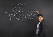 African American woman teacher writing science on chalk black board background Stock Photography