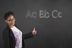 African American woman with thumbs up hand signal alphabet on blackboard background Royalty Free Stock Images