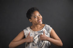 African American woman with thumbs up hand signal on blackboard background Royalty Free Stock Photography