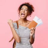 African-american woman with tickets screaming, clenching fist like winner. Pink background, crop royalty free stock photo