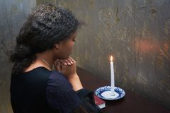 African-American woman to pray at home in the evening. African-American woman to pray at home stock images