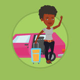 African-american woman traveling by car. African woman waving in front of car. Woman with suitcase standing on the background of open car door. Woman going to Royalty Free Stock Image