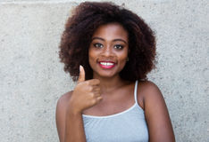 African american woman with typical afro hair showing thumb up. Outdoor in the summer stock photography