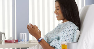 African American woman using cell phone in hospital bed Stock Images