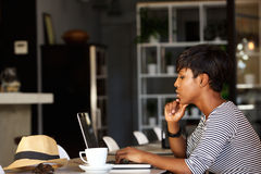 African american woman using laptop at cafe. Side portrait of an african american woman using laptop at cafe restaurant Royalty Free Stock Images