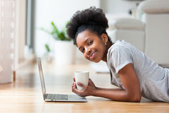 African American woman using a laptop in her living room - Black Stock Photos