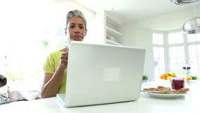 African American Woman Using Laptop In Kitchen At Home stock footage