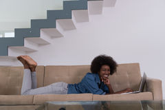African American woman using laptop on sofa Stock Images