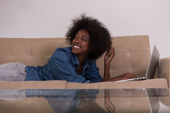 African American woman using laptop on sofa Stock Photo