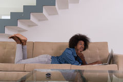 African American woman using laptop on sofa Stock Photos