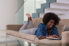 African American woman using laptop on sofa Royalty Free Stock Image