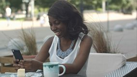 African american woman using phone, while sitting in outside cafe stock photos