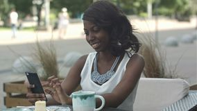African american woman using phone, while sitting in outside cafe stock video