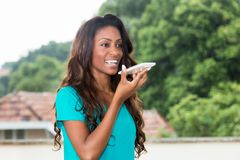 African american woman using voice recognition at phone. Outdoors royalty free stock photo