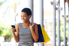 African american woman walking with cellphone and shopping bags Royalty Free Stock Image