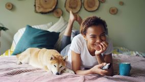 African American woman is watching TV holding remote control pressing buttons and laughing while her pet dog is lying. Young African American woman is watching stock footage
