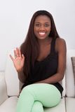 African American woman waving while sitting on sofa Stock Image