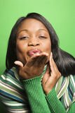 African-American woman wearing green scarf blowing kiss at viewe Royalty Free Stock Images