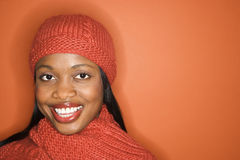 African-American woman wearing orange scarf and hat. African-American mid-adult woman wearing orange scarf and hat on orange background Royalty Free Stock Images