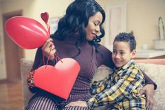 African American woman wit her son. African American boy giving. African American women wit her son. African American boy giving a bouquet of flowers to his Stock Photos