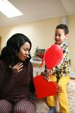 African American woman wit her son. African American boy giving a bouquet of flowers to his mother Royalty Free Stock Photos
