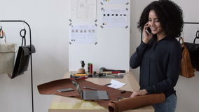 African American woman working in design studio. Standing at table and talking on a cell phone stock video