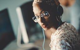 African american woman working on desktop in office. African american woman wearing glasses working on desktop in office Royalty Free Stock Image