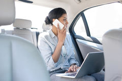 African american woman working with laptop and smartphone in taxi. Concentrated african american woman working with laptop and smartphone in taxi Royalty Free Stock Photo