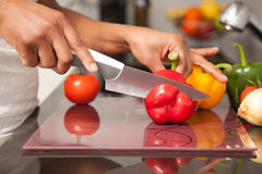 Free African American Womans Hand Slicing A Red Pepper Stock Photo - 29173320