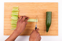 African  American womans hand slicing cucumber Stock Images