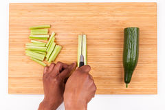 African  American womans hand slicing cucumber Royalty Free Stock Photography