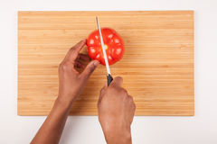African  American womans hand slicing a tomatoe. Flat lay Stock Photo