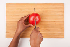 African  American womans hand slicing a tomatoe. Flat lay Royalty Free Stock Photos
