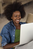 African American women at home in the chair using a laptop Royalty Free Stock Image