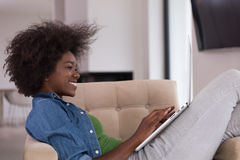 African American women at home in the chair using a laptop Royalty Free Stock Photography