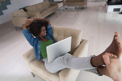 African American women at home in the chair using a laptop Stock Image