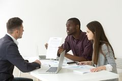 African American worker blaming Caucasian partner for document m. African American worker disagree with Caucasian colleague about contract terms and conditions royalty free stock photography