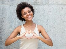 African american young adult woman in love showing heart with ha Stock Photos