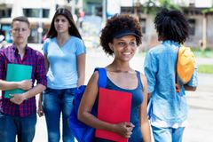 African american young adult woman with students walking in city. African american young adult women with students walking in city in summer stock photo