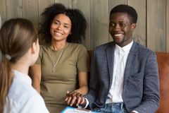 African couple happy to hear good news from doctor counsel. African american young couple holding hands happy to hear good news from doctor, black husband and royalty free stock images