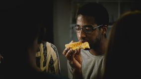African American young man eating pizza at a casual house party. Young people enjoy fast food in the kitchen at home. African American young man in glasses stock video