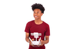 African American young man holding a drone remote control over w Stock Photos