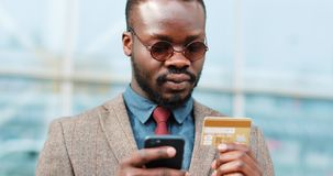 African American young man in sunglasses shopping online with credit card using smart phone in the city.  stock video