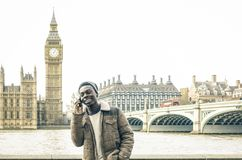 African american young man using mobile smart phone at Thames ri. Verbank in London - Hipster guy male model with modern cell smartphone wearing trendy fashion Royalty Free Stock Photo
