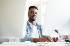 Developing software. African-american young it-manager looking at you while sitting between two monitors and working with software royalty free stock photo