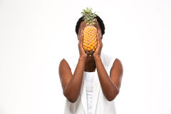 African american young woman covered her face with pineapple Royalty Free Stock Images